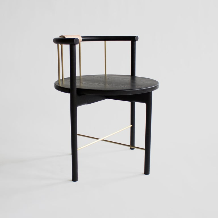 The Lloyd chair, by up-and-coming Baltimore-based design studio Crump & Kwash, is made from solid wood, seen here in blackened oak, but also available in white oak, maple, and walnut. The chair features a barrel back with brass, steel, or bronze