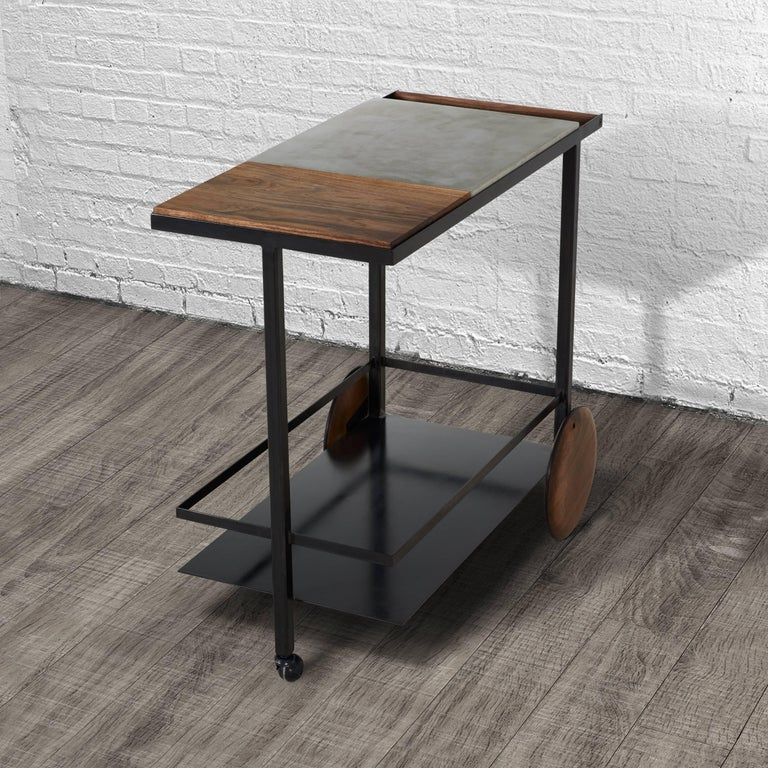 This bar cart is composed of a welded steel frame with lower steel shelf. Upper shelf is a mix of cast-concrete with a removable walnut surface that is finished to be food safe and used as a cutting board or serving tray. The wheels are hand-turned