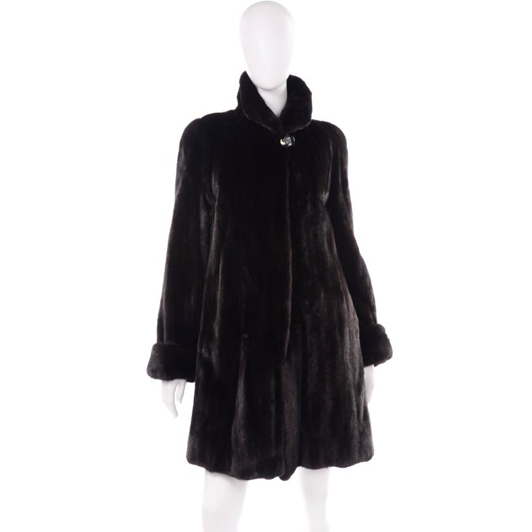 Vintage 1990s dark ranch, black mink fur coat from Blackglama, with a gorgeous adjustable collar. The collar can be formed at the front to be worn completely up, down, or slightly up! It has a large button at the neck, and three hinged metal