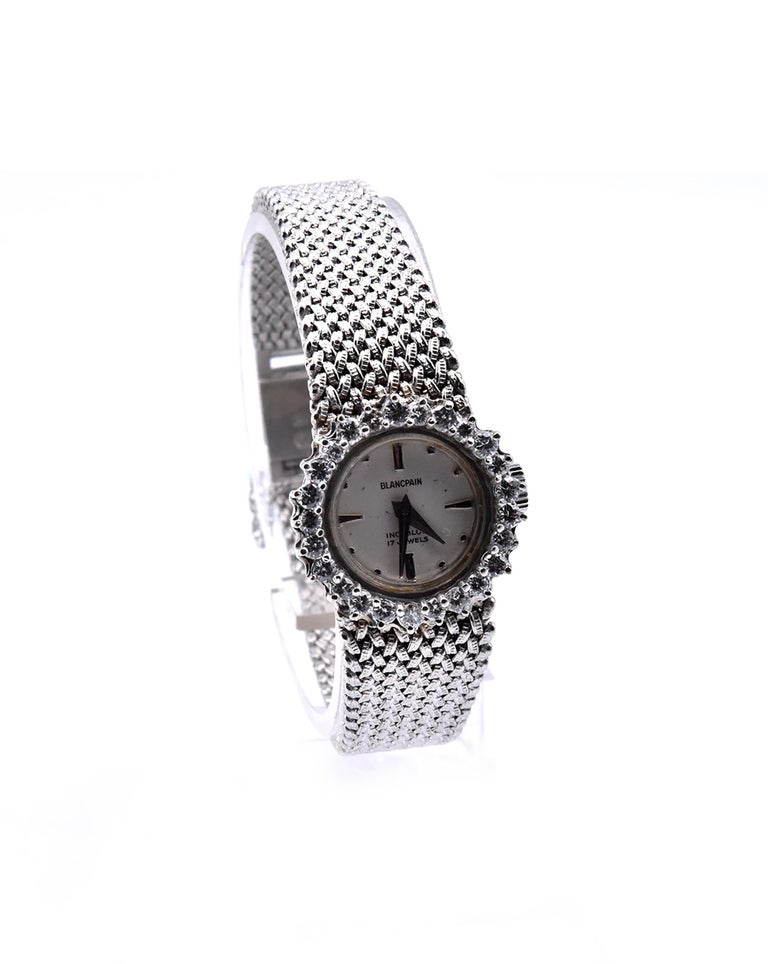 Movement: quartz Function: hours, minutes Case: 20mm round 14K white gold case, .60cttw diamond bezel, push pull crown Band: 18K white gold mesh style bracelet with safety clasp Dial: white dial with silver sticks Serial #: Case Serial