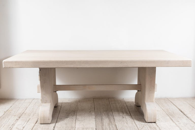 Newly bleached and white washed rectangular farm table with a rounded trestle base.