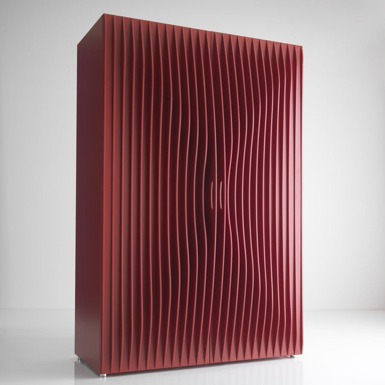 A sculptural piece of functional decor, this wardrobe boasts the dynamism and elegance typical of Karim Rashid's design. Frame, shelves, and doors are made of red-lacquered MDF, boasting a stunning ripple-effect. The interior is illuminated by LED