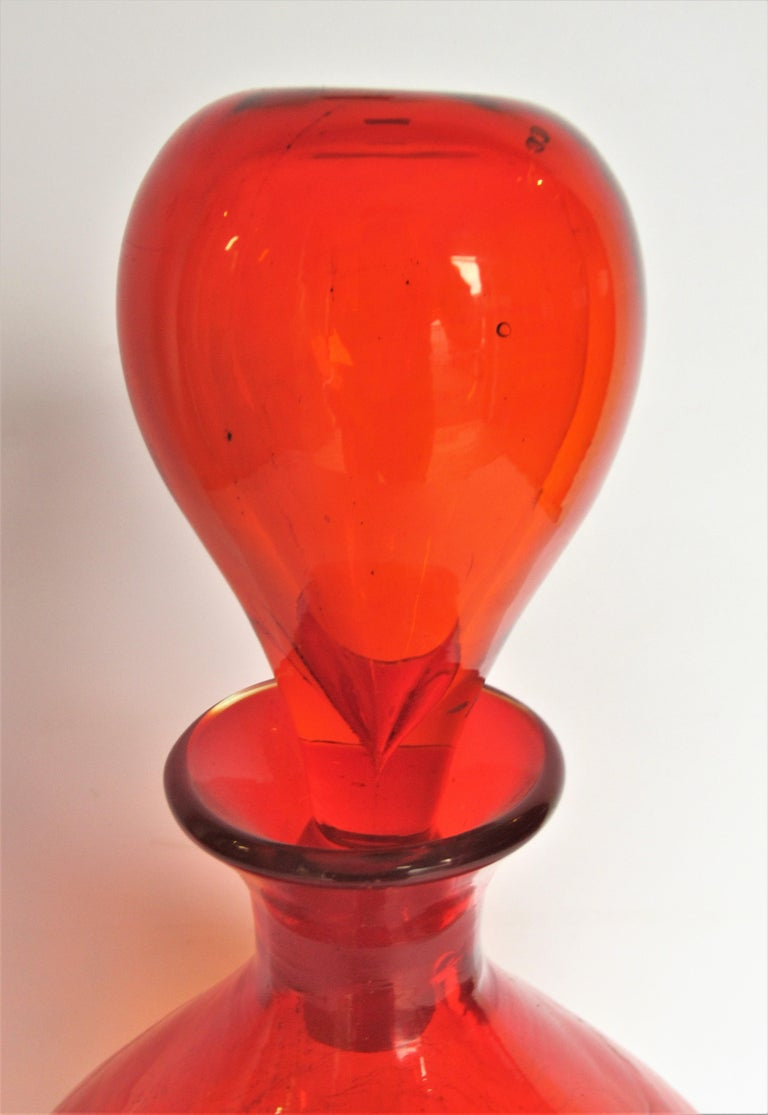 Large bulbous brilliant deep tangerine orange crackle glass decanter bottle by Wayne Husted for Blenko, circa 1960. Bottle with stopper is 13 inches high x 8 inches widest point. Bottle without stopper is 10 1/2 inches high. Look at all pictures and