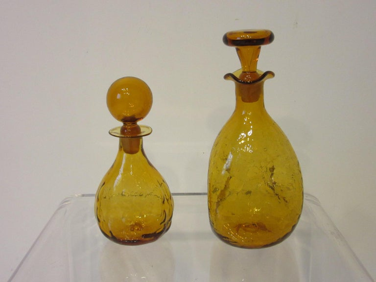 A pair of hand blown decanters with stoppers the smaller one having the bubble pattern and the larger one having the crackle pattern with pinched design. Both are in tangerine color and would work in your bar or as interior accessories make under