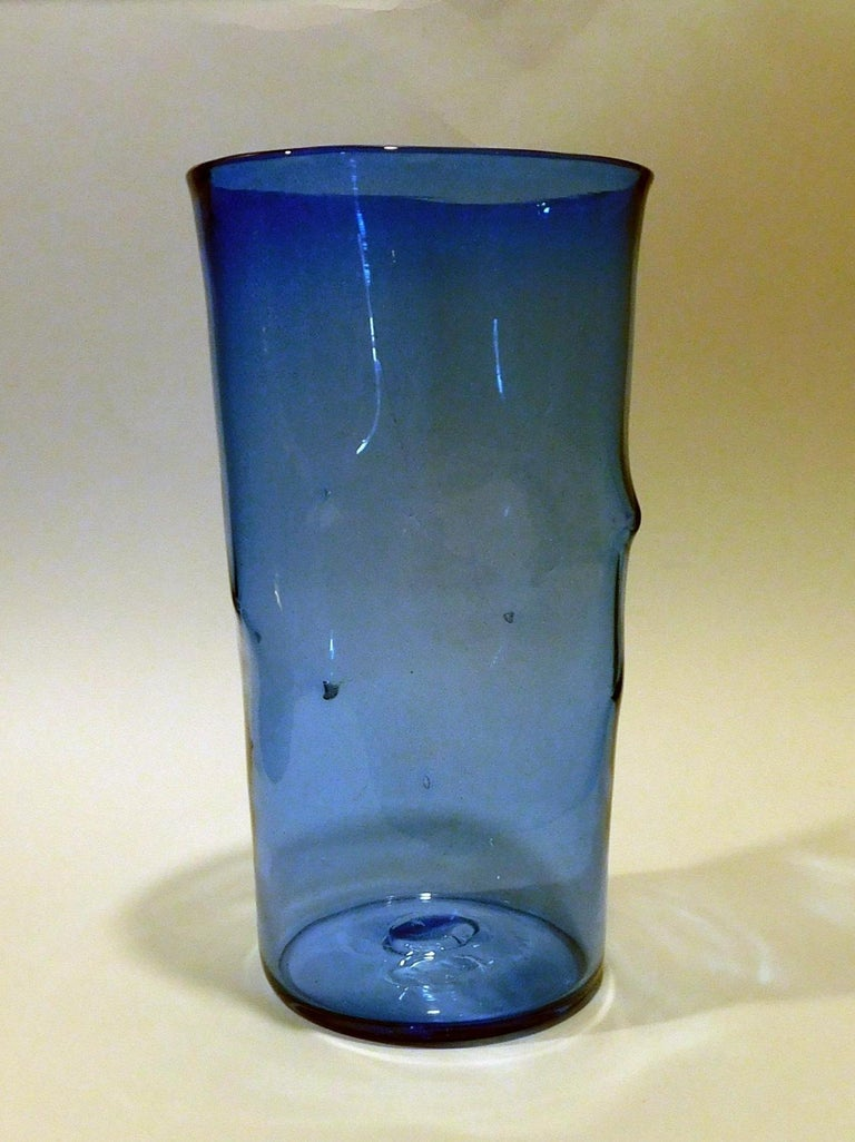 Beautiful blue tall cylindrical pinched vase with Blenko acid etched signature. Measures 12 ½ inches tall. The angular top measures 6 3/4