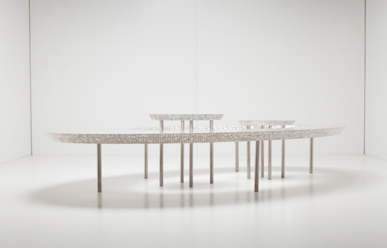 "Supported by metal legs, the iconic ellipse of the coffee bean table is made entirely of mother of pearl. The ""beans"" which nest within the centre can be liberated to suit individual places and layouts."