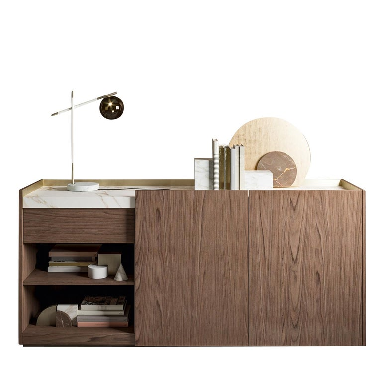 A versatile and timeless piece of functional decor, this sideboard boasts a modern and clean design. Crafted of veneered Canaletto walnut, it features two doors with inner compartments and two open shelves for books, magazines or CDs. The thick top