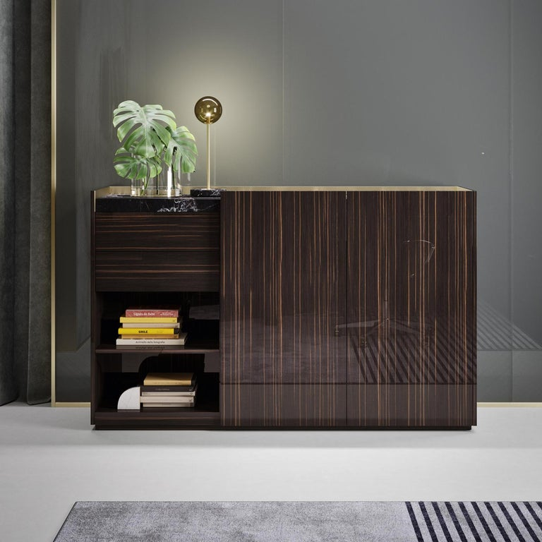 This sideboard boasts a sophisticated and clean design. It comprises a drawer and two doors with push-to-open system, and one open compartment with two shelves. Made of Canaletto walnut veneer with a Calacatta top, it is enriched with hand-brushed