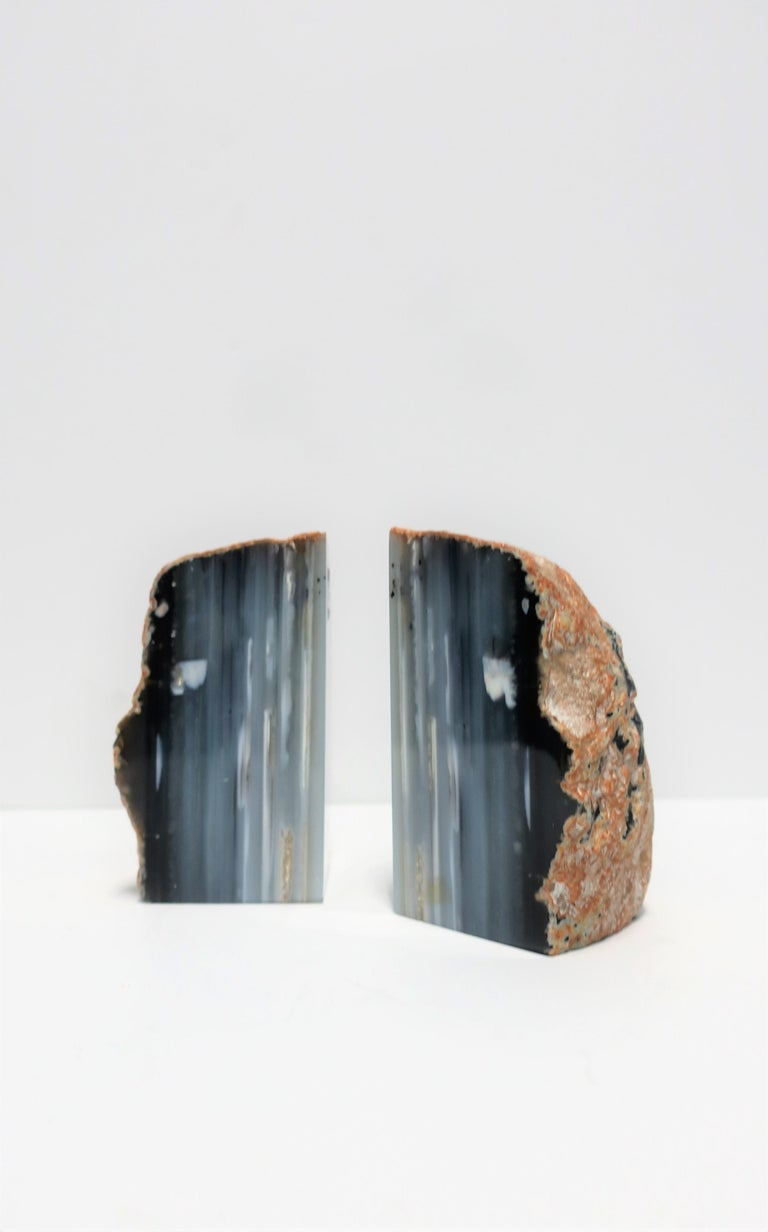 A beautiful pair of blue, grey, and white natural agate onyx bookends or decorative objects. These agate/onyx pieces work well on a bookshelf, or equally well as standalone decorative objects. Colors include shades of blue, grey, and white.  Each
