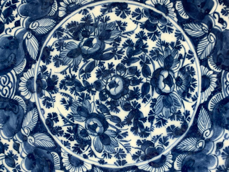 The entire surface of this beautiful blue and white Dutch Delft charger is covered in deep cobalt blue coloring. The center of the charger is filled with hand-painted peonies; while the wide border is painted with a net-like pattern of peonies,