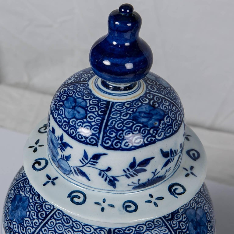 We are pleased to present this Dutch delft blue and white antique ginger jar painted in a deep cobalt blue. The jar is decorated all around with sprays of chrysanthemums. The top, shoulders, and base are painted with scrolling vines and flower