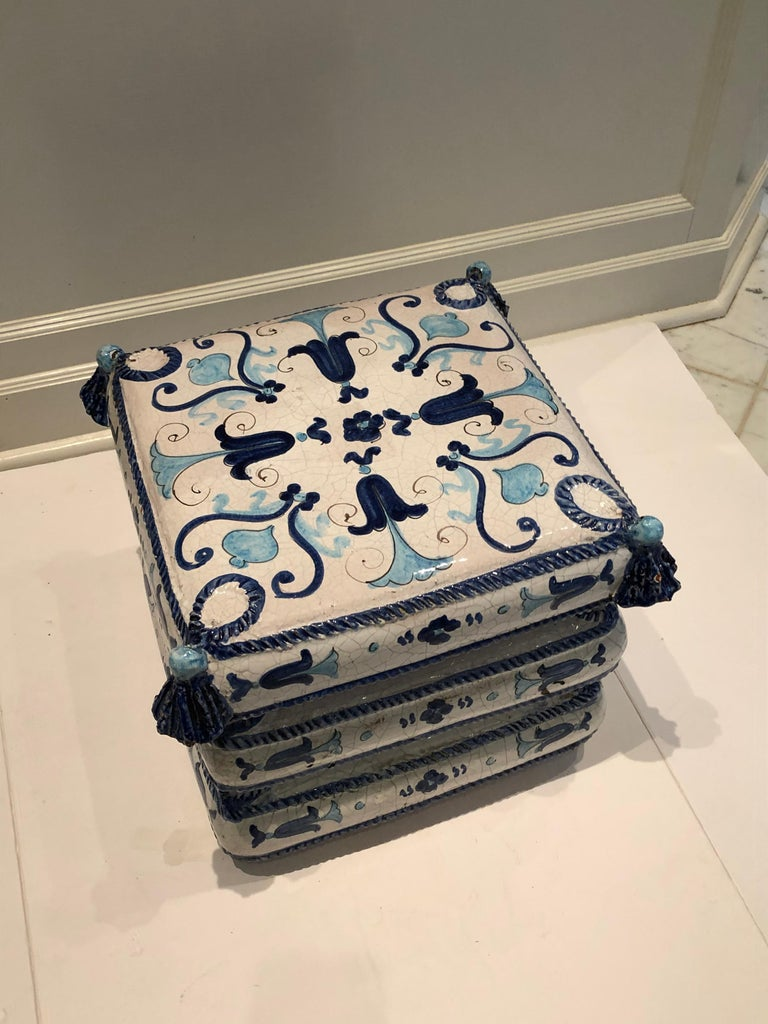 Stylish blue and white ceramic garden seat end table from Italy. Charming hand painted details in varying shades of blue which include bell flowers, roping and tassels. Lovely used indoors or on the patio.
