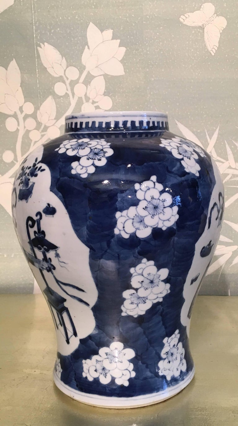 A 19th century Chinese blue and white temple jar with prunus design. Design with reserves of antiques and symbols.