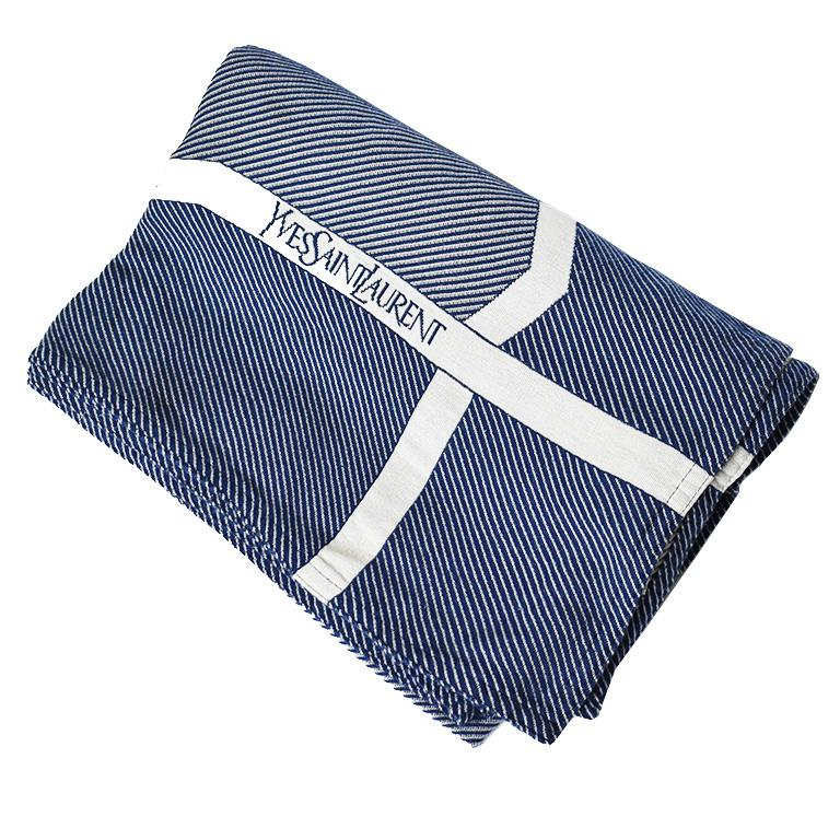 Beautiful blue and white woven vintage Yves Saint Laurent blanket. This piece features blue and white woven wool fabric with the YSL logo on one side against a white background.