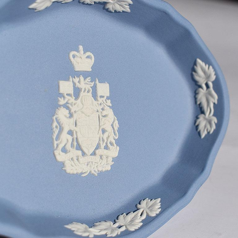 Jasperware dish in blue and white. This oblong dish with scalloped edges is blue with white floral decorations at the edges. At the center is the Canada coat of arms. Signed at bottom Special Edition Wedgwood, made in England.  Size: 4.32