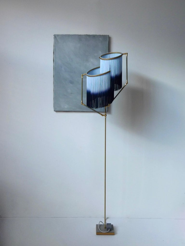 Blue charme floor lamp, Sander Bottinga  Dimensions: H 153 x W 38 x D 25 cm. Hand-sculpted in brass, leather, wood and dip dyed colored Fringes in viscose. The movable arms makes it possible to move the circles with fringes in differed