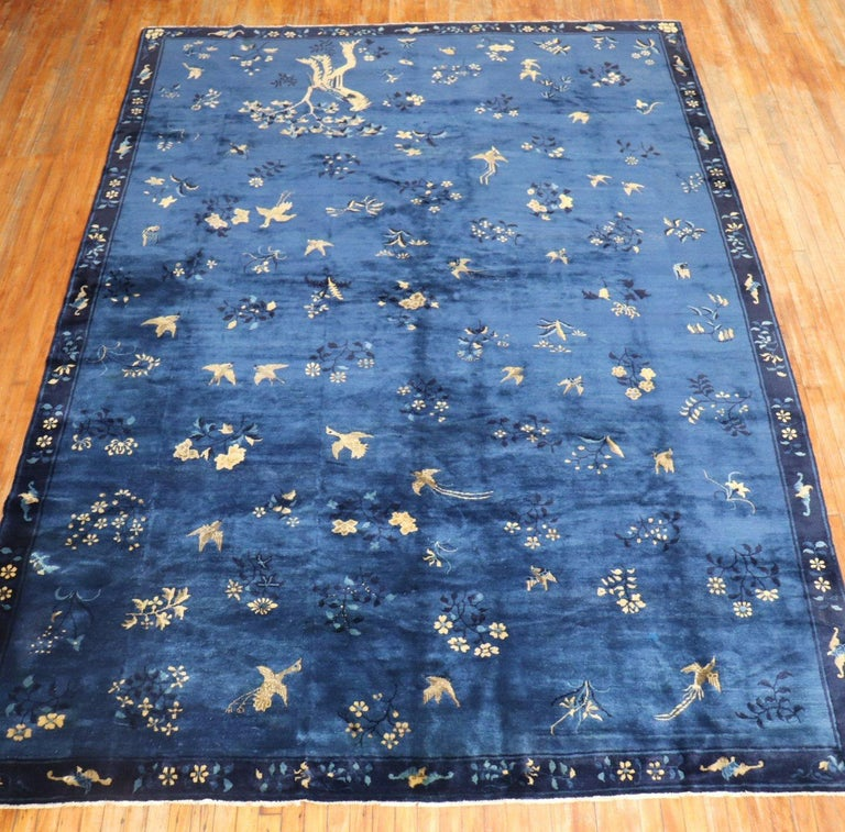 An early 20th century fine quality Chinese pictorial rug with birds and pigeons floating on a blue field