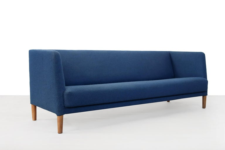 Blue Danish design sofa designed by famous designer Hans J. Wegner and produced by Johannes Hansen in the 1960s in Denmark. The sofa has solid oak legs and is upholstered in blue wool fabric from Kvadrat Tonica 2 color 773. This beautiful sofa is