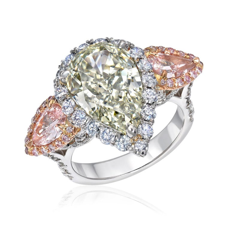 Green Pink Diamond Ring - Ultra exclusive 5.16 carat Natural Fancy Deep Grayish Yellowish Green diamond, VS2, pear shape, surrounded by round brilliant Natural Fancy Blue diamonds, flanked by a pair of Natural Fancy Pink diamond pear shapes weighing