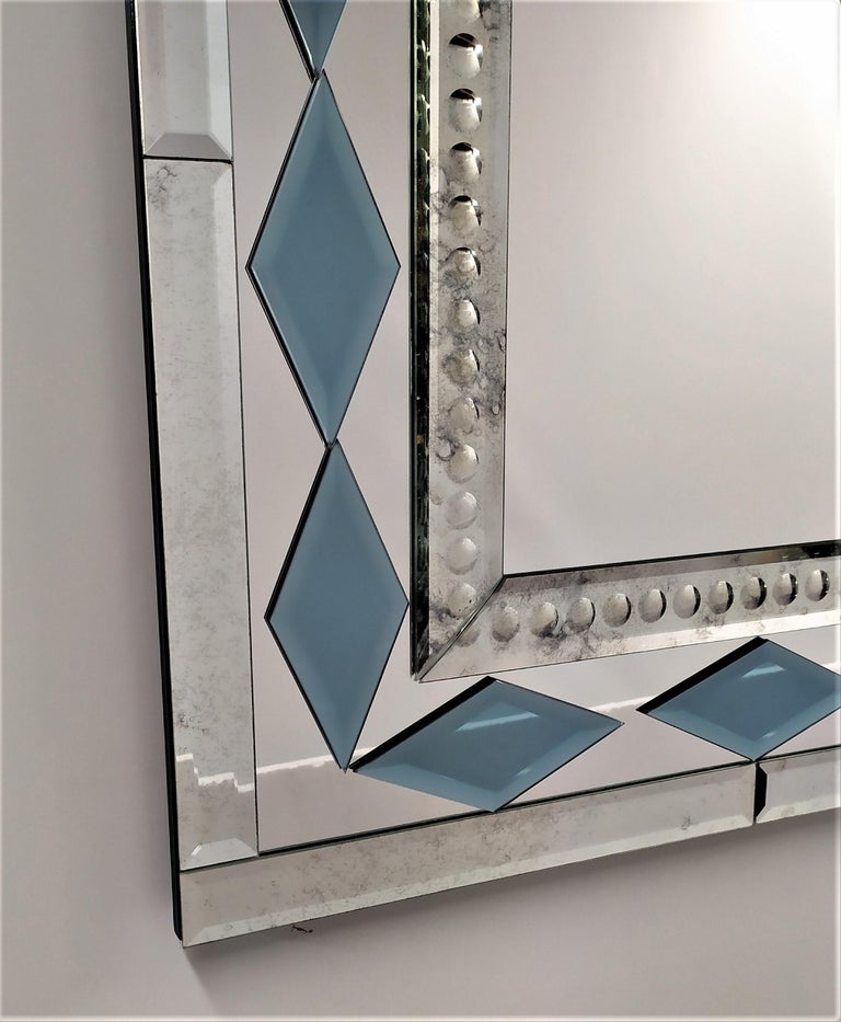 Rectangular murano glass mirror, from the twenty-first century, composed of beveled, antiqued and bubbles engraved bands by hand, with the insert of the blue crystal rhombuses faceted like diamonds all handmade, produced in a limited mirror made by