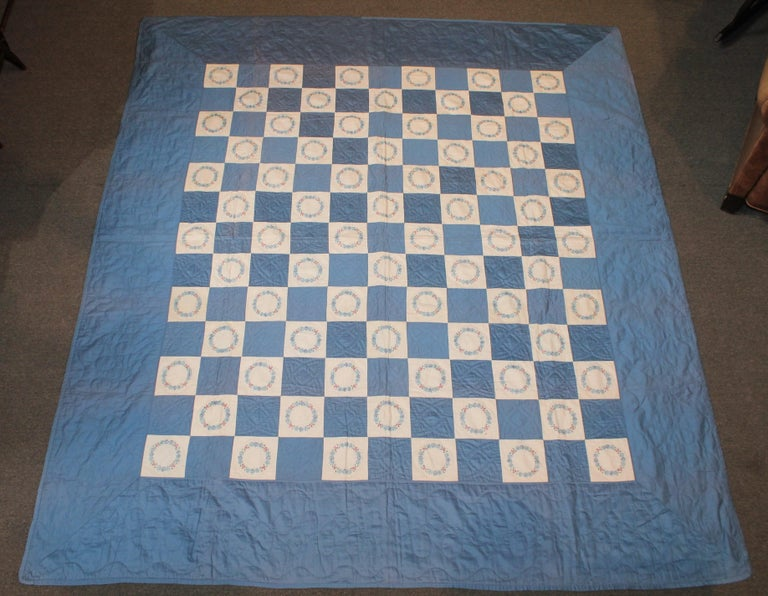 This finely quilted blue and white sateen quilt is in fine condition. Minor fold fade in areas.