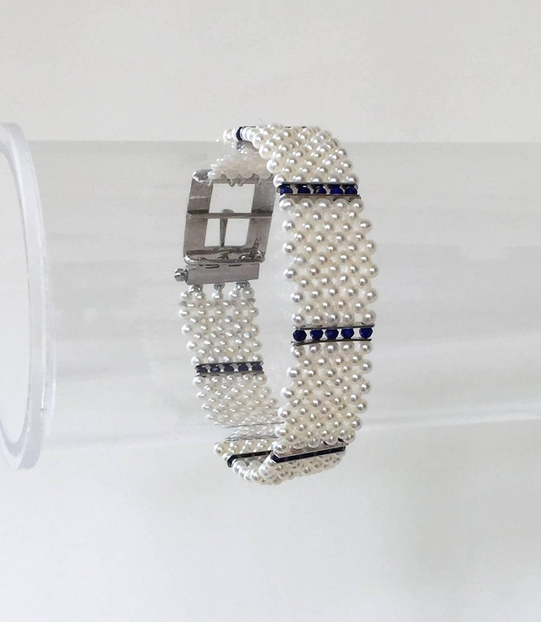 This delicate bracelet gracefully sits on the wrist. With an elegant and re-enforced weave of the finest white pearls accented by lapis lazuli faceted beads and 14k white gold dividers, the bracelet has a striking design. The finishing piece is a