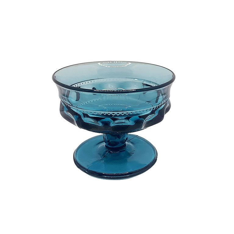 A set of 8 verdigris blue-faceted drinking glasses. This glassware set includes eight drinking glasses in a deep blue color glass. The body of each cup is short and coupe style. They are decorated on the sides with