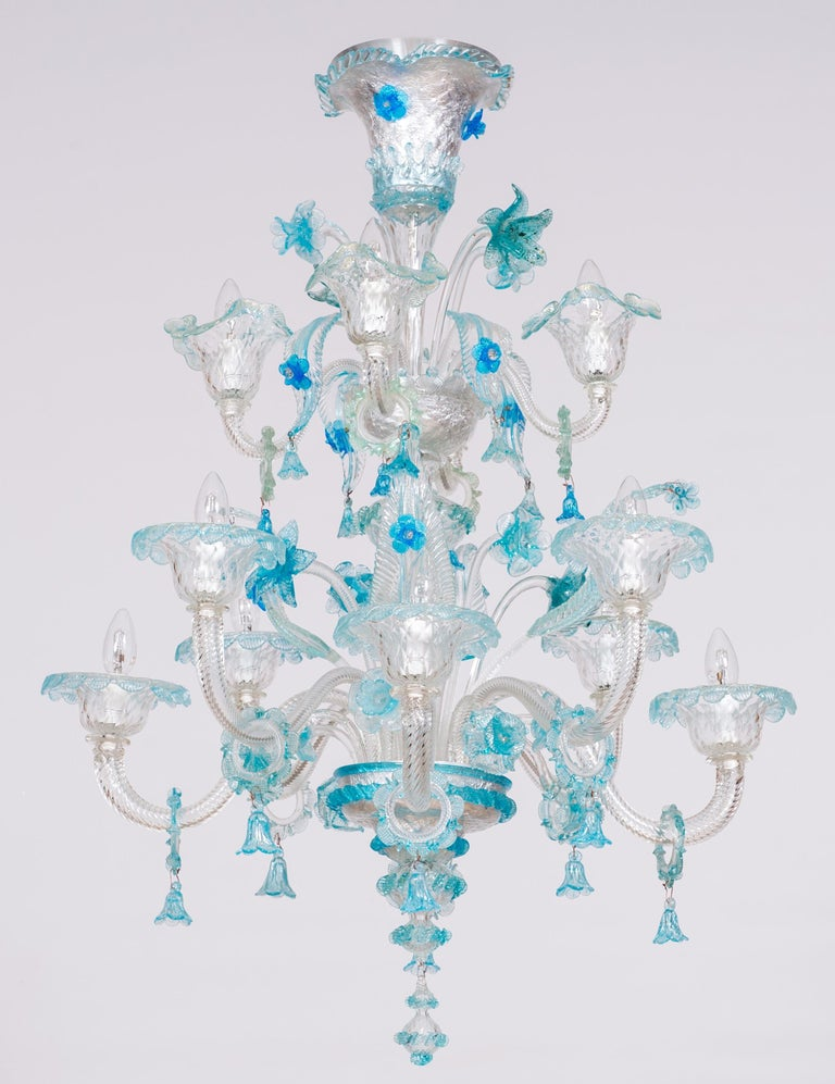 Contemporary Italian Murano glass chandelier with blue flower-shaped decorations. This fine chandelier is entirely hand crafted utilizing the traditional Murano glass artisanal methods. It is composed of 12 arms distributed in two rows. Beautiful