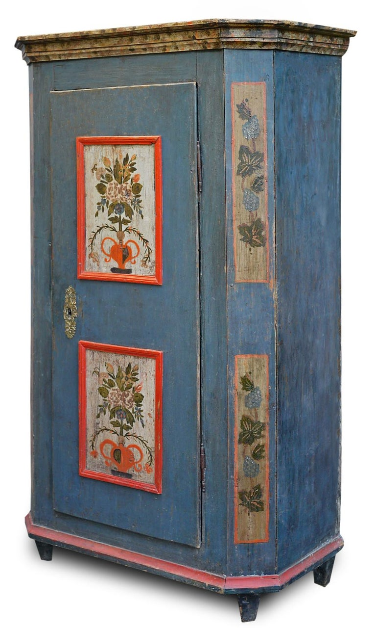Antique blue painted Tyrolean wardrobe  H.190 cm - L.105 cm - P.45 cm  Tyrolean wardrobe entirely painted in blue with floral decorations, with a linear profile and pleasant geometric composure.  On the door, two carmine-colored frames have as