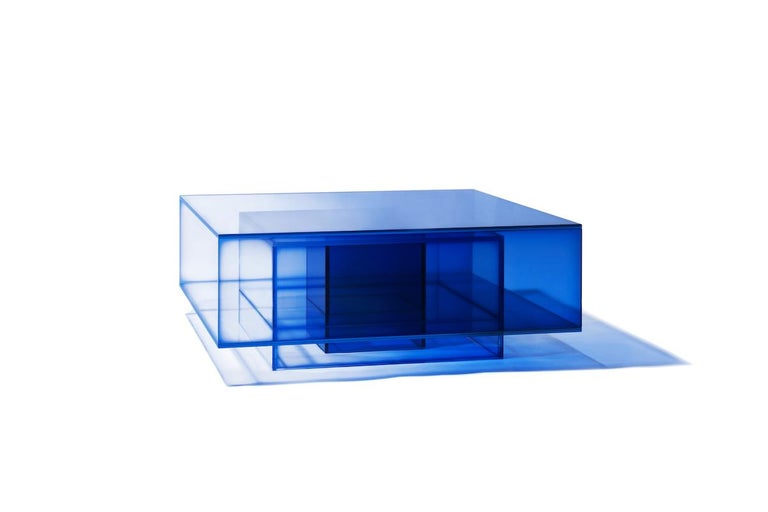 This coffee table is made of laminated glass in blue color. Size and color are customizable upon request. 