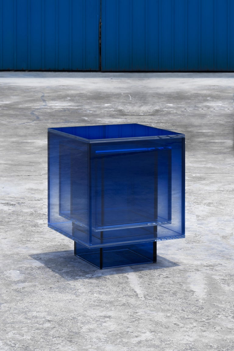 This square table is made of laminated glass in blue color. Size and color are customizable upon request.   Studio Buzao is an experimental design studio. It tempts to breakthrough the difference between product and artwork by immersing the