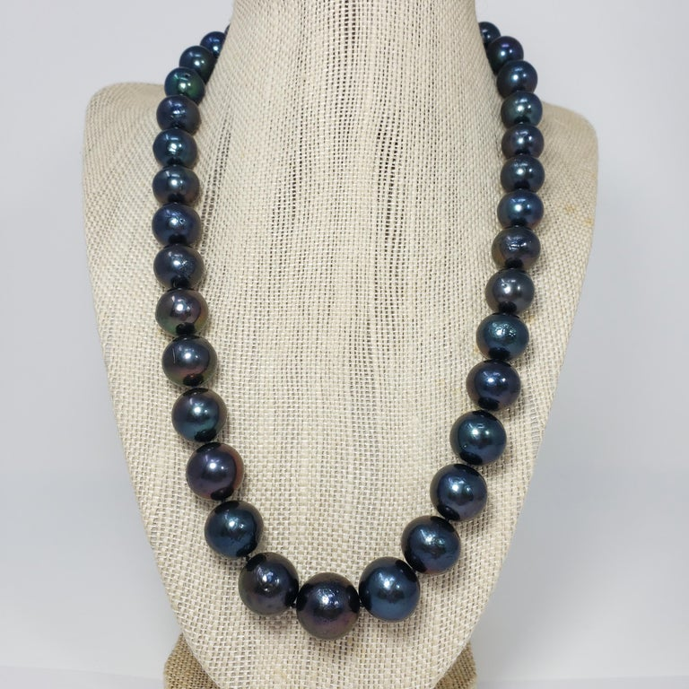 A sophisticated strand of grduated Tahitian pearls with a dark blue-green tint, accented with a sterling silver clasp. This necklace is sleek and sophisticated!  Hallmarks: 925 Pearls range from 11.6mm to 15mm in diameter