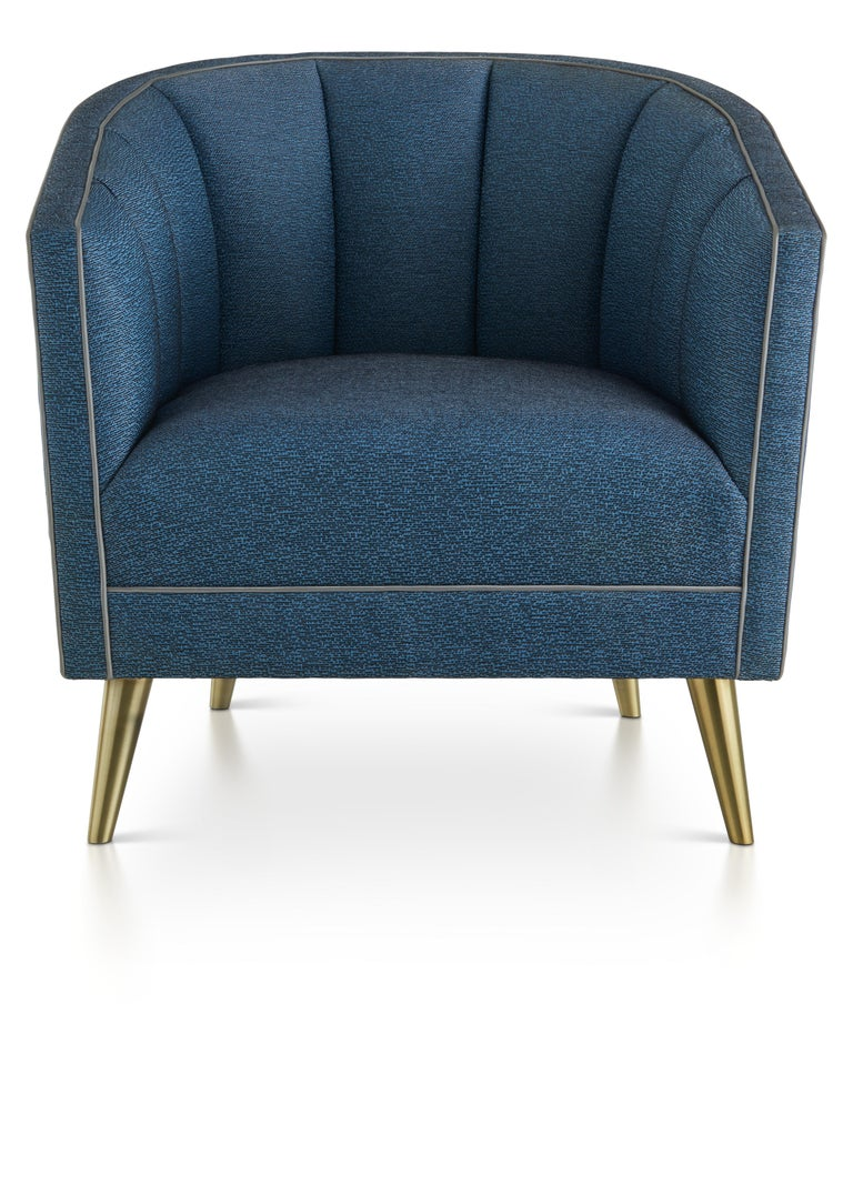 This elegant deep-seated armchair with scalloped back detail adds unique refinement to any room.   The design can be upholstered in complementary fabrics, including a deep blue, with contrasting piping and finished with glistening fine brushed brass