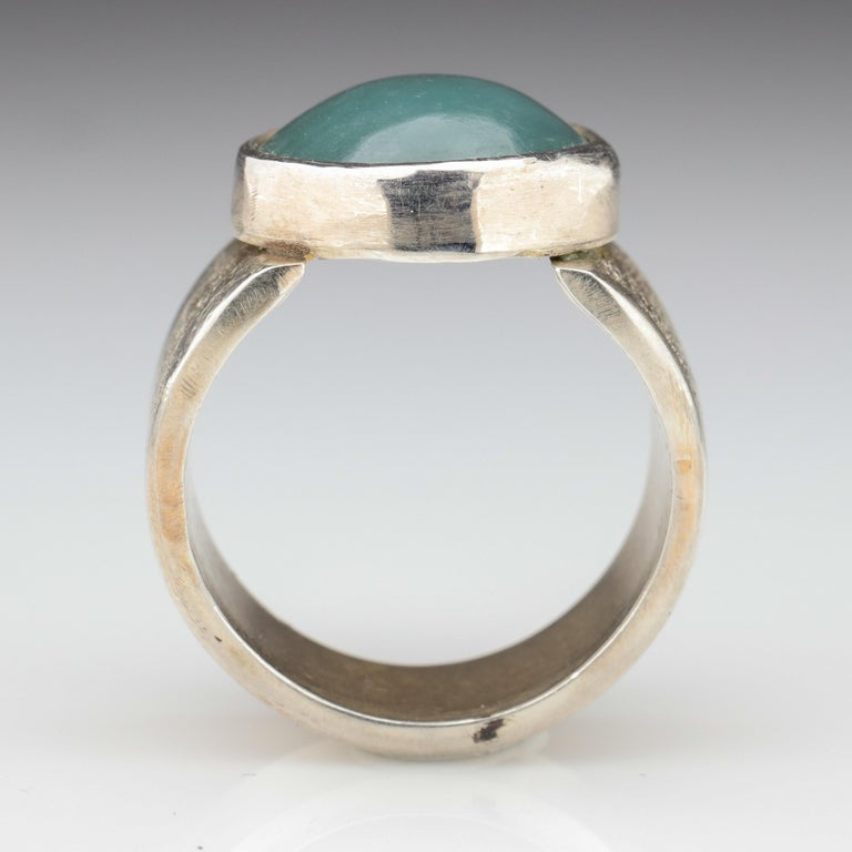 Blue is among the most uncommon —the rarest— colors of jadeite jade. And this contemporary hand-fabricated silver ring features a glowing, translucent bluish-green cabochon of certified natural and untreated jadeite jade from Burma. The particular
