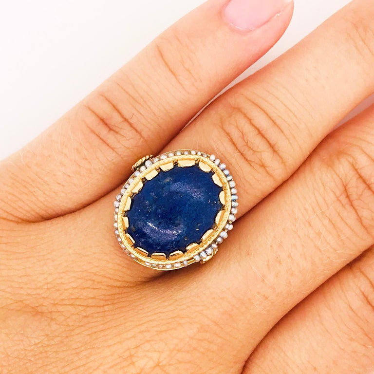 This Circa 1960 blue lapis and seed pearl ring is so interesting and eclectic. The blue lapis is 6 carats and oval in shape with a beautiful color with the natural gold veining in the gemstone.  The halo of seed pearls are all genuine, cultured