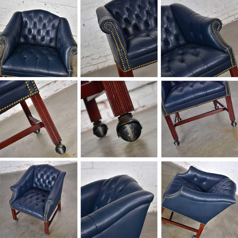 Handsome blue leather rolling Captain's chair in a Campaign or Chippendale style game or tub chair on painted ball casters. In wonderful vintage condition. Age-appropriate condition with a few imperfections as one would expect with a vintage piece.