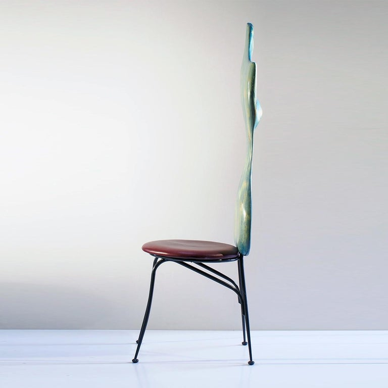 The chair is part of a limited series of unique and vibrant pieces of furniture crafted from the wood of tree trunks damaged or derived from industrial waste processing. Finished in light blue whitewash paint, the sinuous back in recovered maple