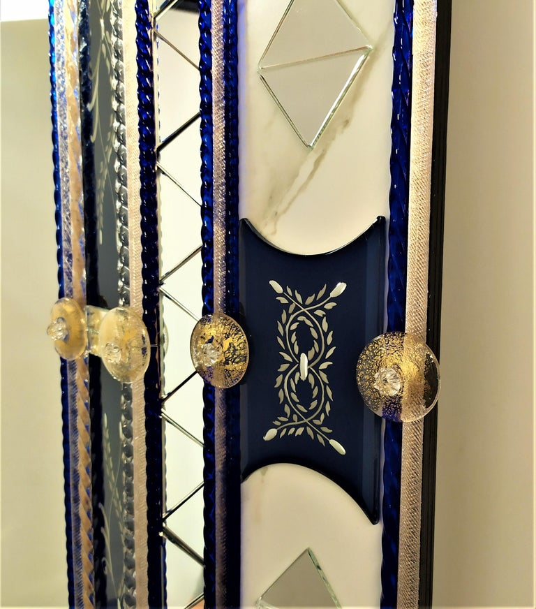 Mirror in Murano glass, with bands and beveled pieces engraved, silvered with pure silver in blue color, with insertion of details in clear mirror in the shape of a triangle, Murano glass rods in crystal and blue color Madonna on a gold background,