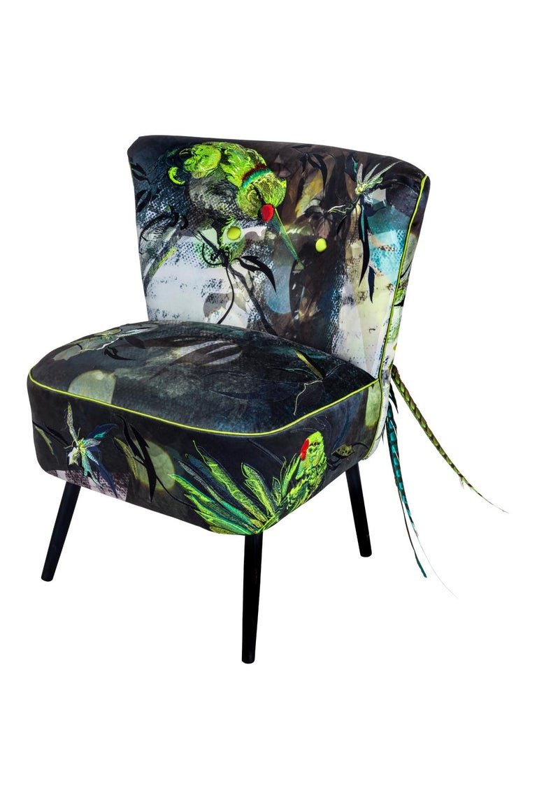 The blue parrot cocktail chair is a magnificent statement chair of printed velvet and intricate embroidery on a bespoke frame developed from original vintage models. Migrating creatures, from escaped parrots to foxes and rabbits, are shown within