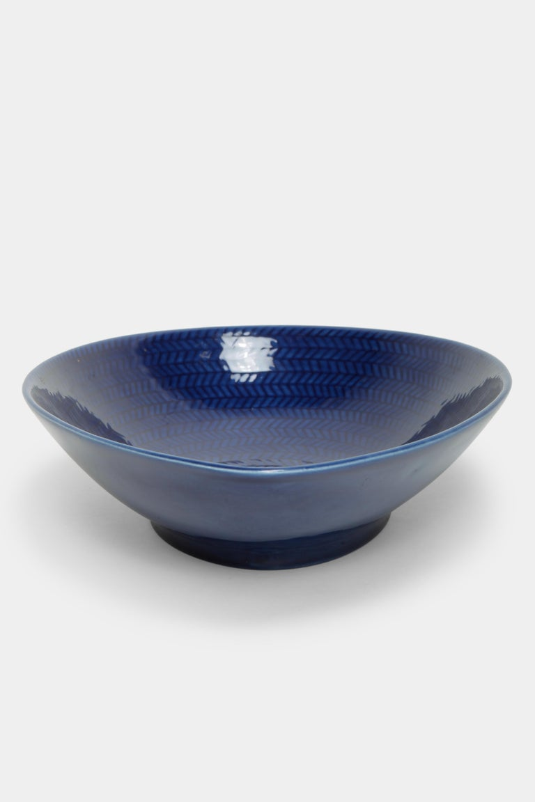 Ceramic bowl by Hertha Bengtson designed for the Swedish manufacturer Rörstrand in the 1950s. Belongs to the Blå Eld (blue fire) series. The elongated bowl has a deep blue color with an intricate pattern on the inside.