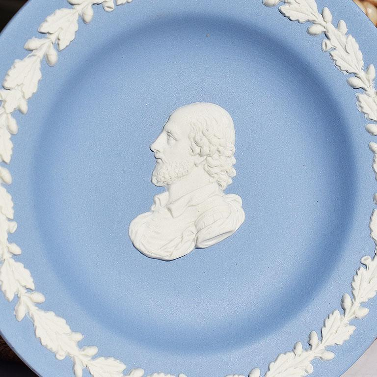 Jasperware dish in blue and white. This round dish is blue with white floral decorations at the edges. At the center, a man with a beard is featured. Signed at bottom Wedgwood Made in England.  Specifications: 4.32