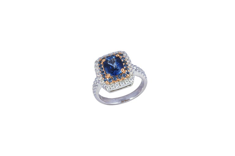 Centered with an oval Blue Sapphire (2.14 carats) and surrounded by Blue Sapphire 0.40 carats and Diamonds 0.58 carats, this ring is uniquely created with a combination of 18 karat White and Rose Gold Settings.     Width: 1.5 cm Length: 1.8 cm Ring