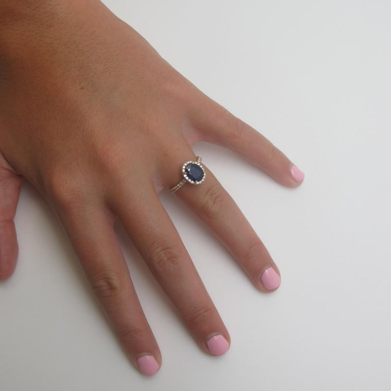 """This ring has that undeniable class, that really makes a piece of jewelry truly """"timeless."""" A deep, royal blue, oval sapphire weighing 2.16 carats and measuring 8.58 x 6.84 mm is encircled by 24 round brilliant cut diamonds (.24 carats total"""