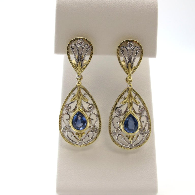 Made of 18k white and yellow gold, these masterfully crafted and hand engraved earrings are enhanced by 2 beautiful blue sapphires (2.29cts tw) and 12 white diamonds (0.48cts tw). These earrings are large, but not heavy; very comfortable to wear.