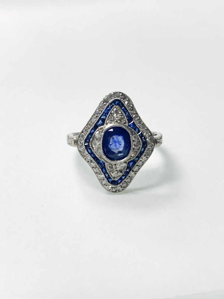 Blue sapphire and diamond engagement ring hand crafted in platinum.  The details are as follows :  Blue sapphire cushion weight : 1 carat  Blue sapphire baguette weight : 0.79 carat  Diamond weight : 1.75 carat ( GH color and VS clarity )  Metal :