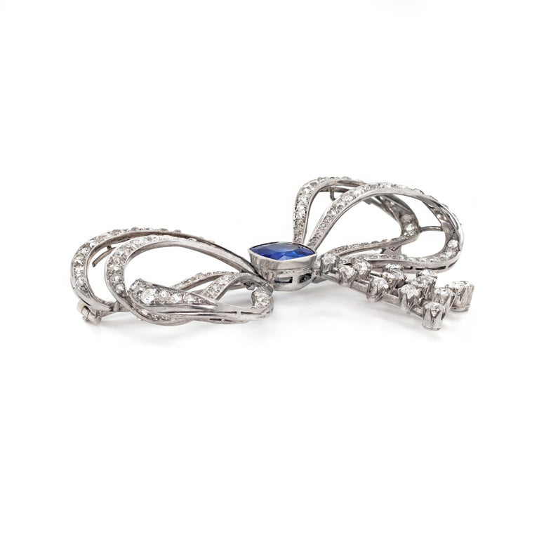 This exceptional 1930's handmade piece features a cushion shaped blue sapphire weighing approximately 5.00ct in an open back, rub over setting, mounted in the centre of a bow. The ribbons are pavé set with 136 old mine cut diamonds and the spray is
