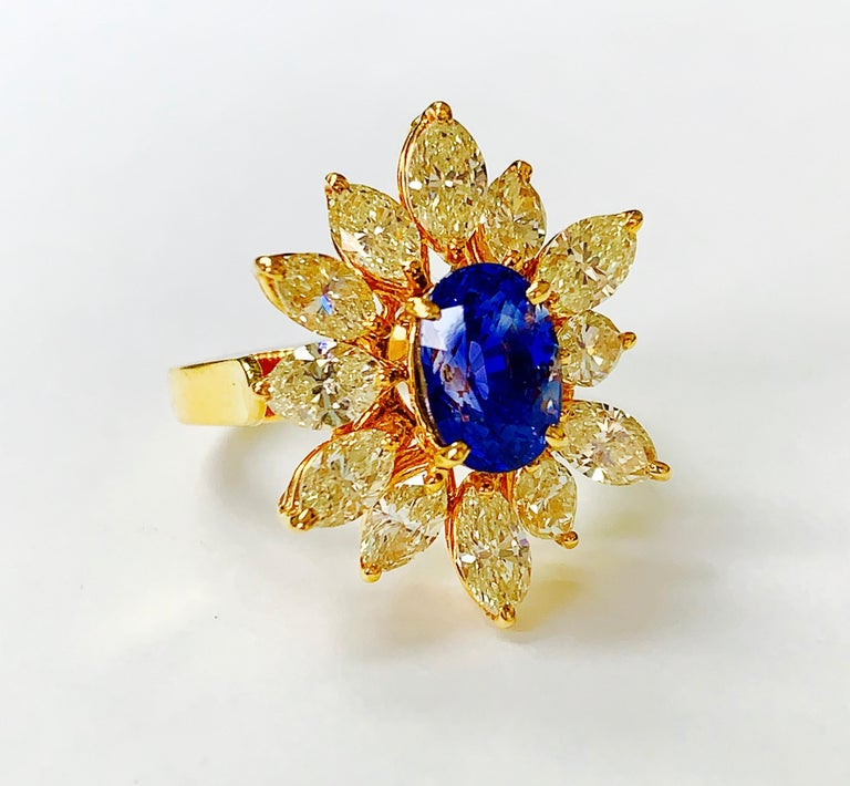 Oval Cut Blue Sapphire and Yellow Diamond Ring in 18 Karat Yellow Gold For Sale