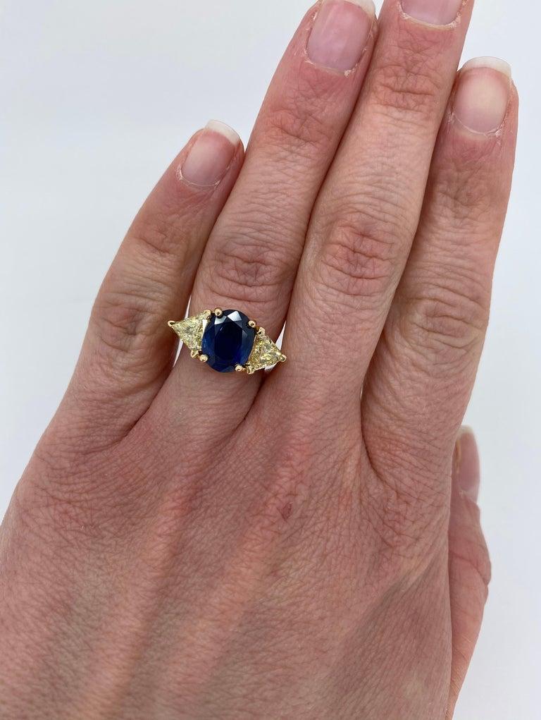 Unique Blue Sapphire and light yellow diamond ring crafted in 14k yellow gold.  Gemstone: Blue Sapphire & Diamond Gemstone Carat Weight: Approximately 10.12mm x 8.25mm Oval Cut  Diamond Cut: Trilliant Cut Diamonds Average Diamond Color: Light