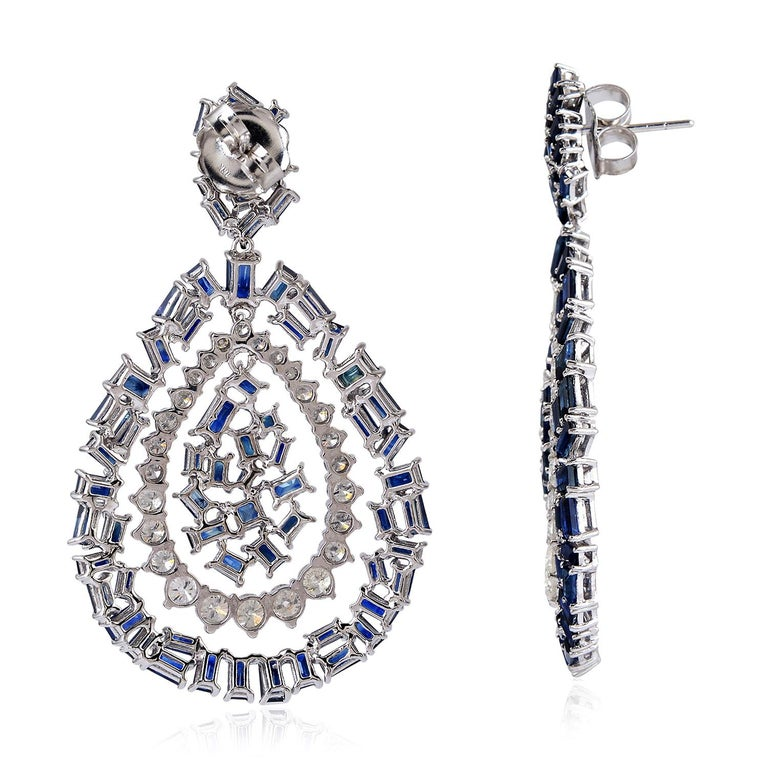 Cast from 18-karat gold, these stunning baguette diamond drop earrings are hand set with 15.37 carats blue sapphire and 4.43 carats of glittering diamonds.  FOLLOW MEGHNA JEWELS storefront to view the latest collection & exclusive pieces.