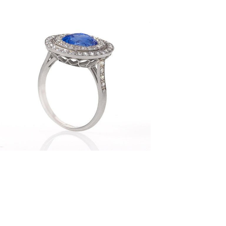 A Late 20th Century platinum cluster ring with blue sapphire and diamond. The ring has an oval blue sapphire weighing 5.08 carats, and 50 round-cut diamonds with an approximate total weight of 1.02 carats with a G-H color and VS clarity. The ring is